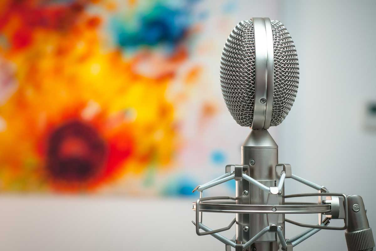 How to create brand tone of voice guidelines - Shows a microphone with a colourful background