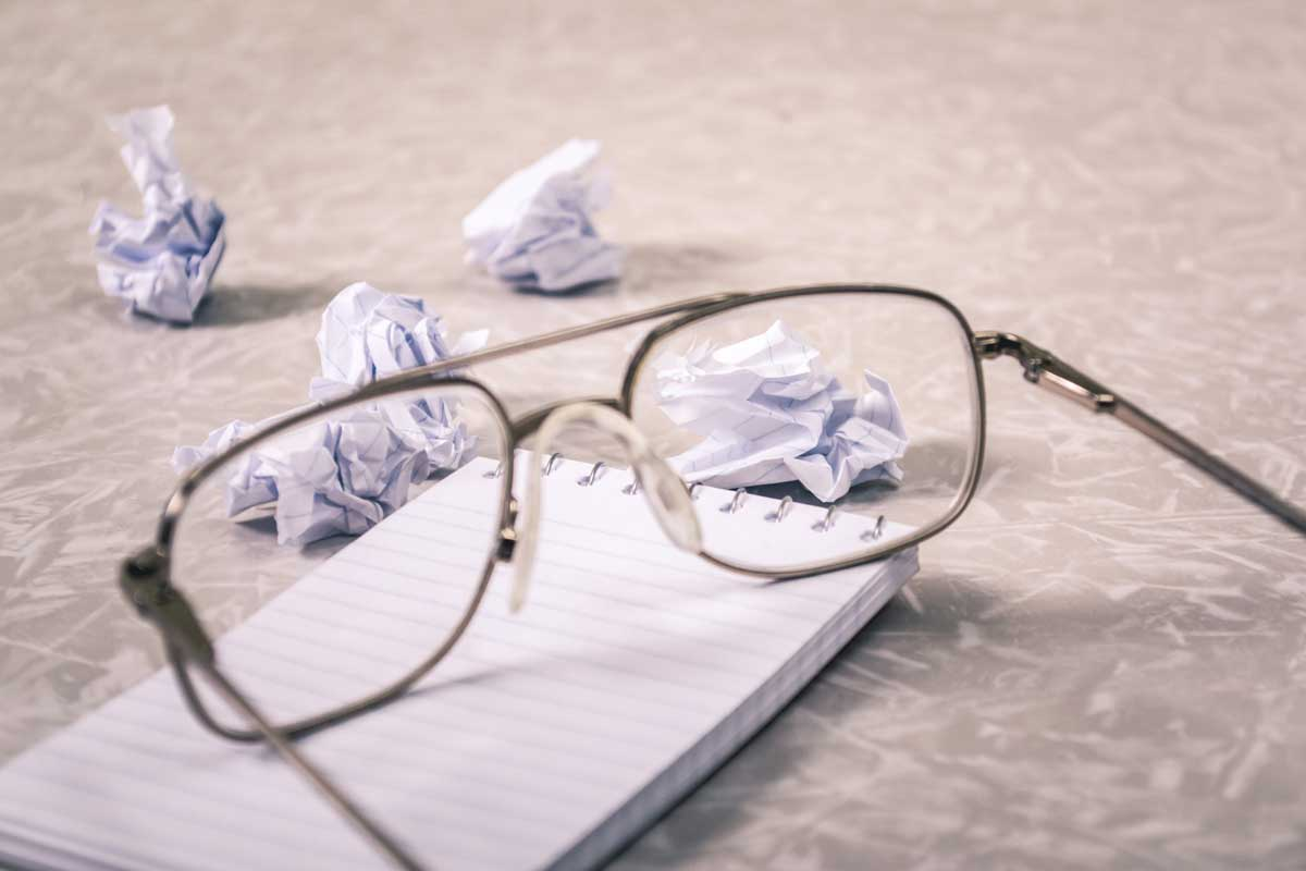 A pair of glasses alongside scrunched up paper