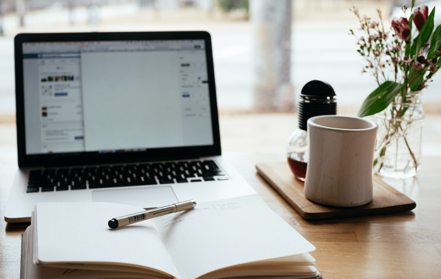 How to become a copywriter UK - Shows a pen and paper in front of a laptop